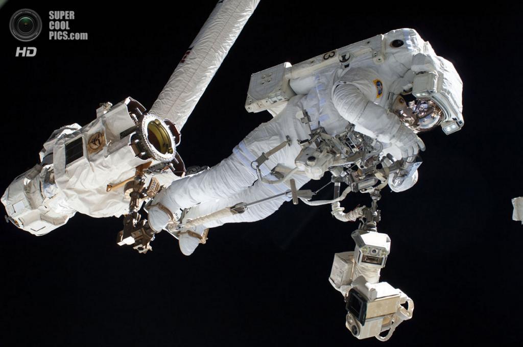 Canadarm2 удерживает Луку Пармитано. (NASA)