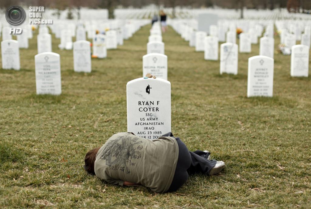 США, Арлингтон, Виргиния. 11 марта 2013 года. 25-летняя Лесли Койер лежит у могилы своего брата Райана, служившего в Ираке и Афганистане. Он умер от осложнений после ранения на поле боя. (REUTERS/Kevin Lamarque)