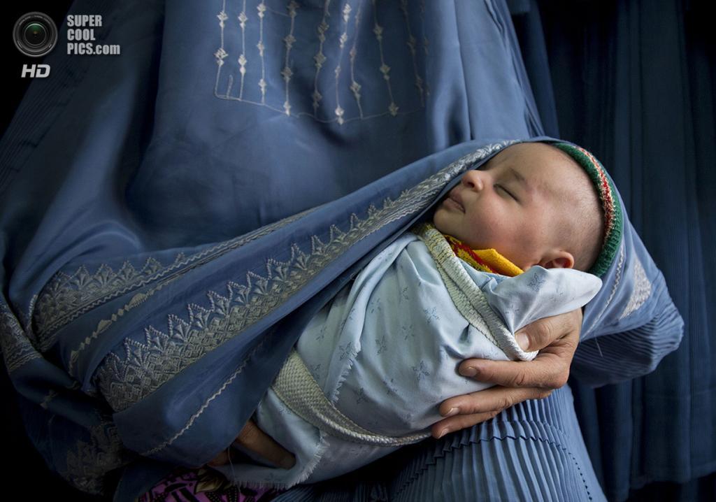 Афганистан. Кабул. 11 апреля 2013 года. Афганка в парандже держит на руках своего новорожденного ребёнка. (AP Photo/Anja Niedringhaus)