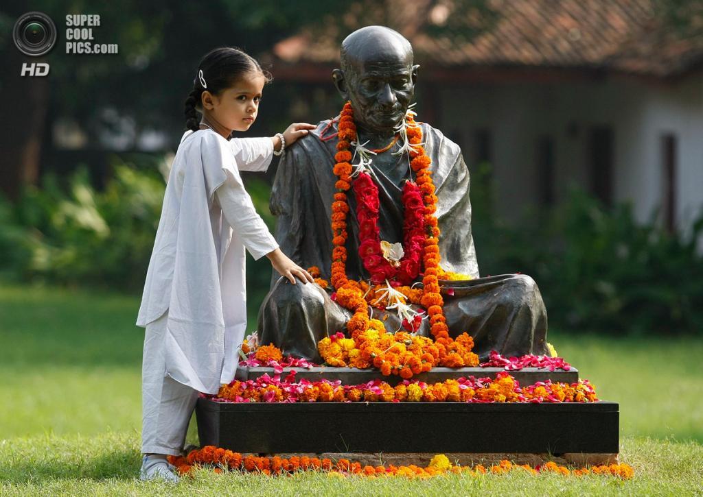 Индия. Ахмадабад, Гуджарат. 2 октября. Девочка позирует у памятника Махатмы Ганди для фотографии. (REUTERS/Amit Dave)