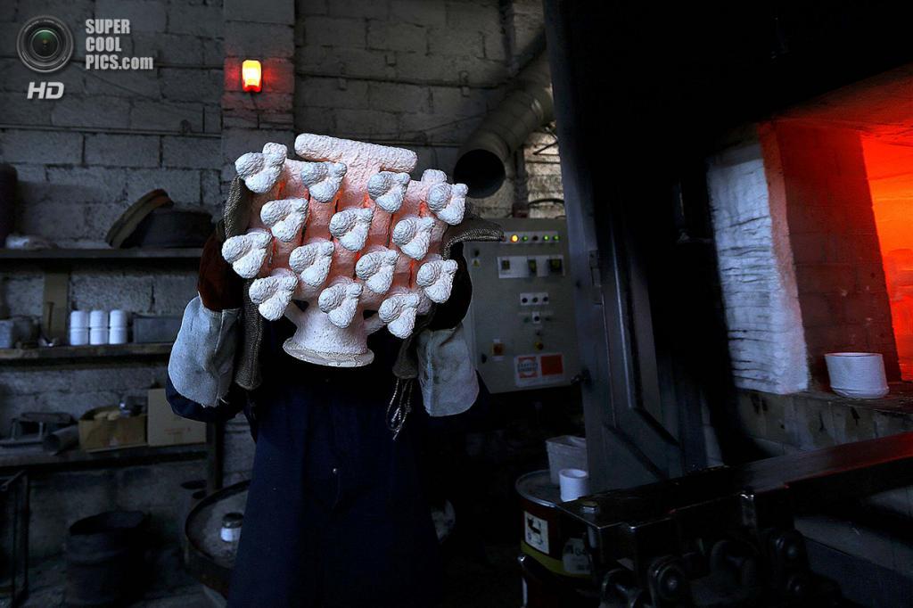 Великобритания. Саутгемптон, Англия. Работник Polycast Limited Томас О'Донохью держит пылающую форму для статуэток. (REUTERS/Stefan Wermuth)