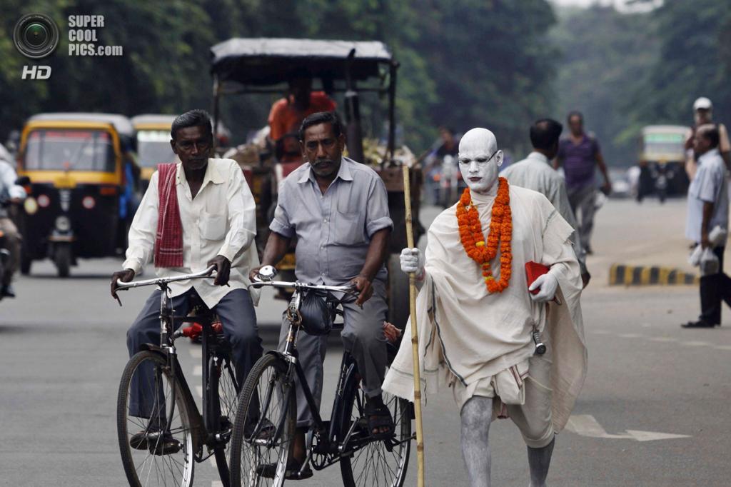 Индия. Бхубанешвар, Орисса. 2 октября. Индус в образе Махатмы Ганди на оживлённой улице. (AP Photo/Biswaranjan Rout)