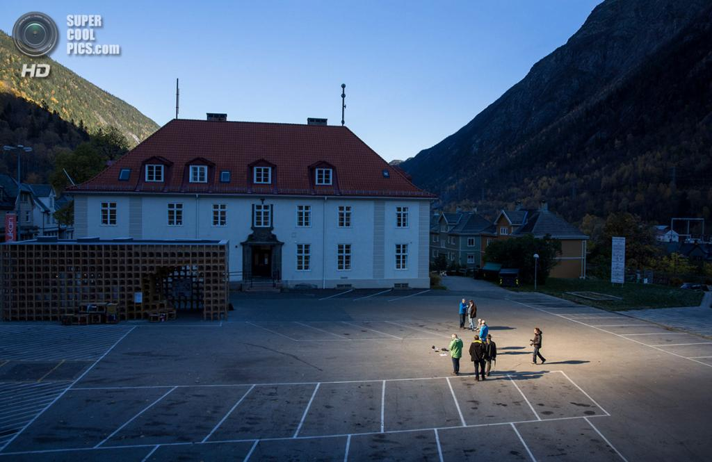 Норвегия. Рьюкан, Телемарк. 18 октября. Рьюканцы у ратуши наблюдают за работой гигантских зеркал, установленных на высоте 450 метров над долиной для отражения солнечных лучей. (REUTERS/Tore Meek/NTB Scanpix)