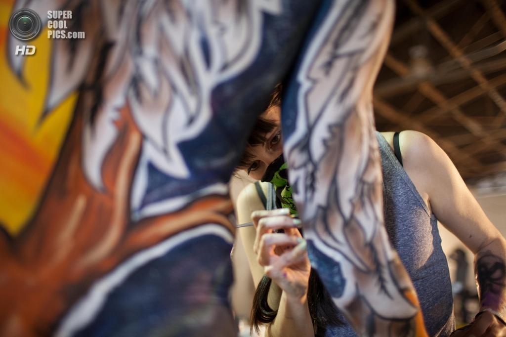 США. Атланта, Джорджия. 28 сентября. Художница Элизабет Шиффер из Техаса разукрашивает модель Лон Лоусон на фестивале «Living Art America / Bodies as a Work of Art». (AP Photo/Branden Camp)
