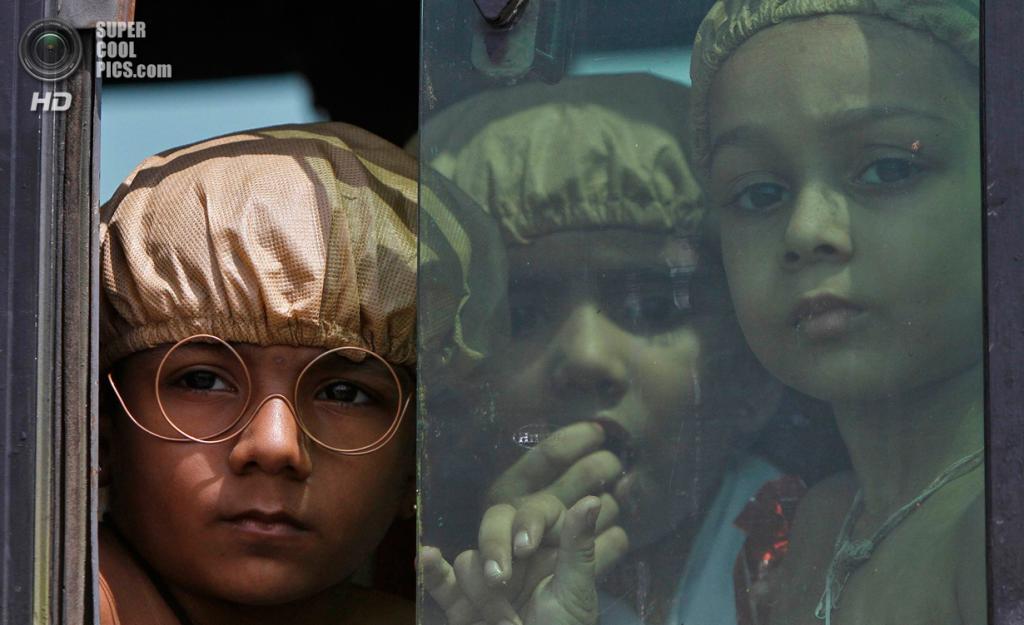 Индия. Ченнаи, Тамилнад. 2 октября. Индийские дети в образе Махатмы Ганди выглядывают из школьного автобуса. (REUTERS/Babu)