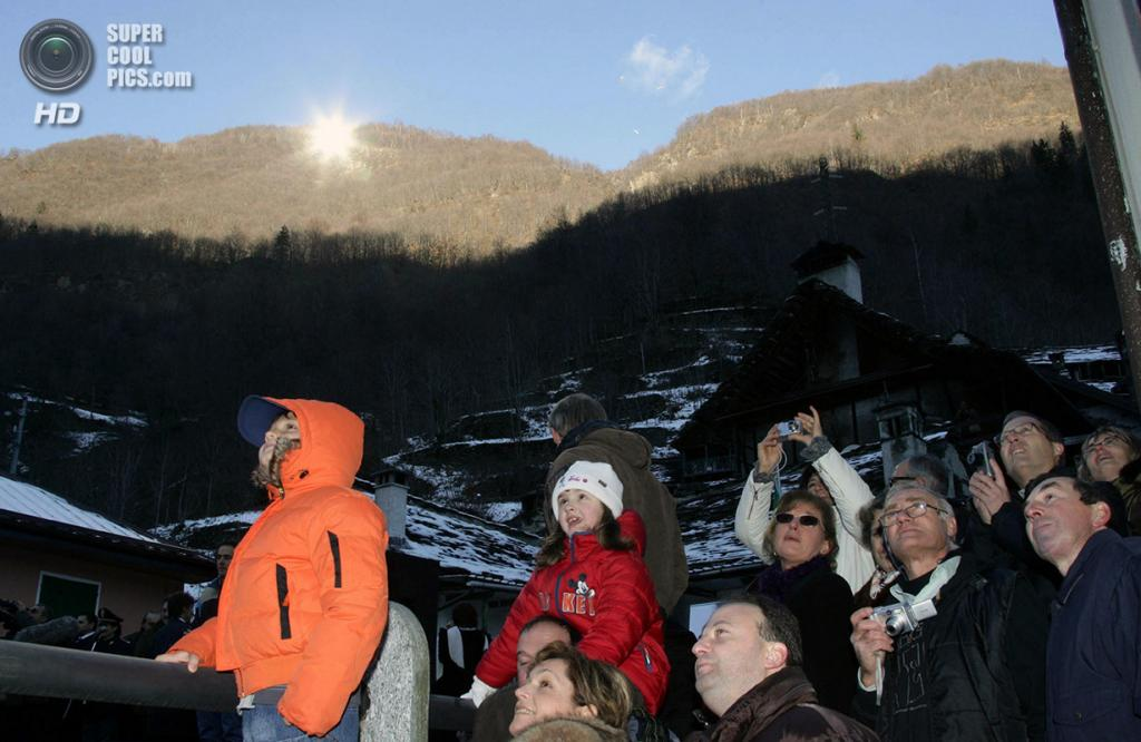 Италия. Виганелла, Пьемонт. 16 декабря 2006 года. Местные жители радуются свету солнца, отражаемому зеркалами с высоты 1 100 метров на горе Скаджола. (REUTERS/Remy Steinegger)
