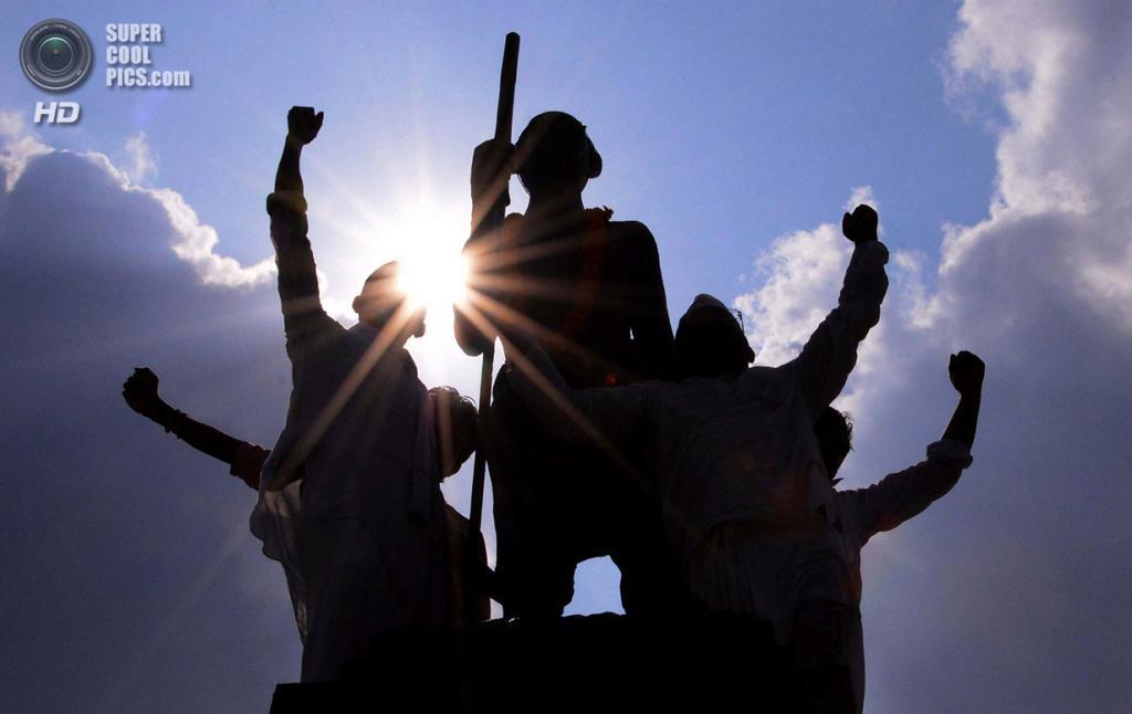 Индия. Амритсар, Пенджаб. 1 октября. Социальные работники вешают гирлянды на памятник Махатмы Ганди накануне 144-й годовщины его рождения. (NARINDER NANU/AFP/Getty Images)