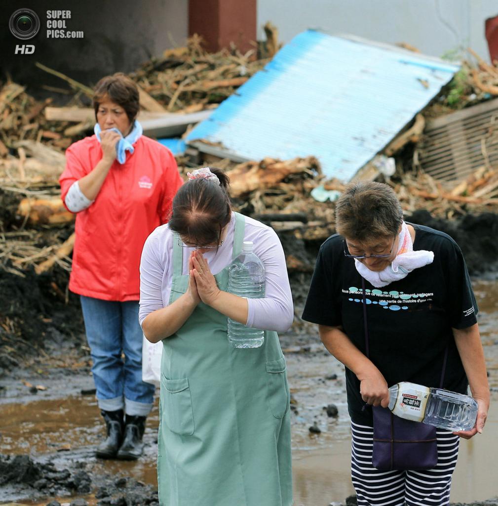 Япония. Осима, Токио. 16 октября. Местные жители склони головы в молитве на месте разрушений. (AP Photo/Kyodo News)