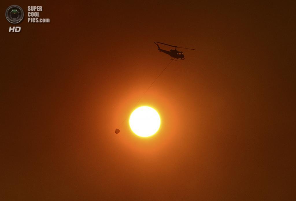 Австралия. Новый Южный Уэльс. 20 октября. Пожарный вертолёт с водой спешит на тушение лесного пожара в окрестностях Сиднея. (REUTERS/Stringer)