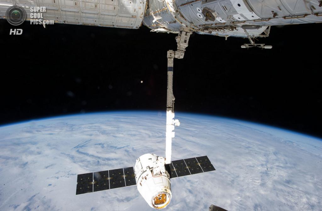 26 марта. Роботическая рука МКС CanadArm2 держит космический корабль SpaceX «Дракон» во время его стыковки со станцией. (NASA)