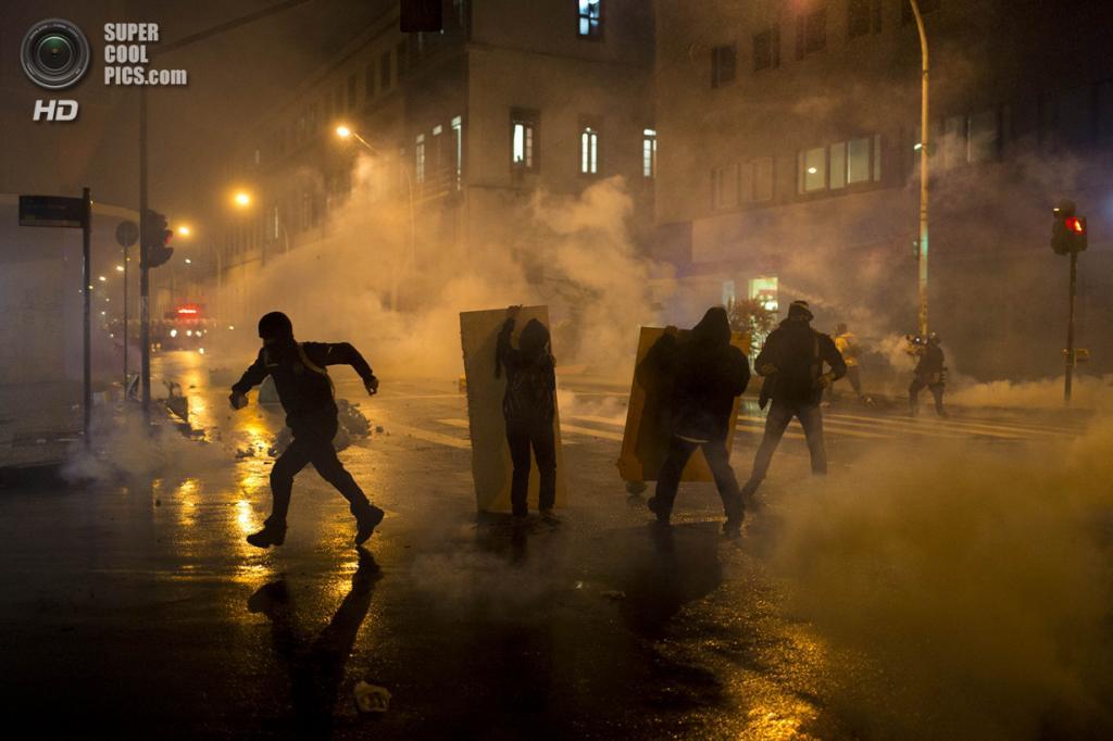 Бразилия. Рио-де-Жанейро. 7 октября. Во время демонстрации, переросшей в ожесточённое противостояние с полицией, в поддержку учителей, которые около двух месяцев требуют повышения зарплаты. (AP Photo/Felipe Dana)