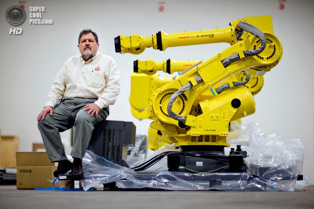 США. Атланта, Джорджия. 15 января. Совладелец и президент Factory Automation Systems Россер Приор сидит рядом со своим новым промышленным роботом. (AP Photo/David Goldman)