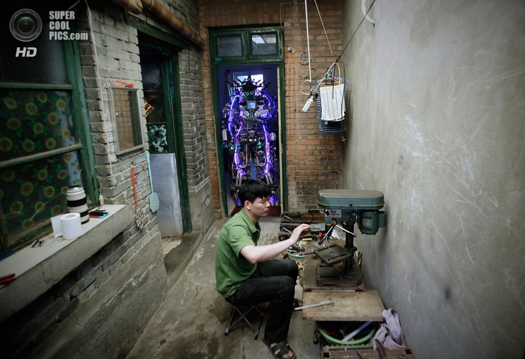 Китай. Пекин. 15 мая. Изобретатель Тао Сянли работает над усовершенствованием своего самодельного робота, претенциозно названного «Король инноваций». (REUTERS/Suzie Wong)
