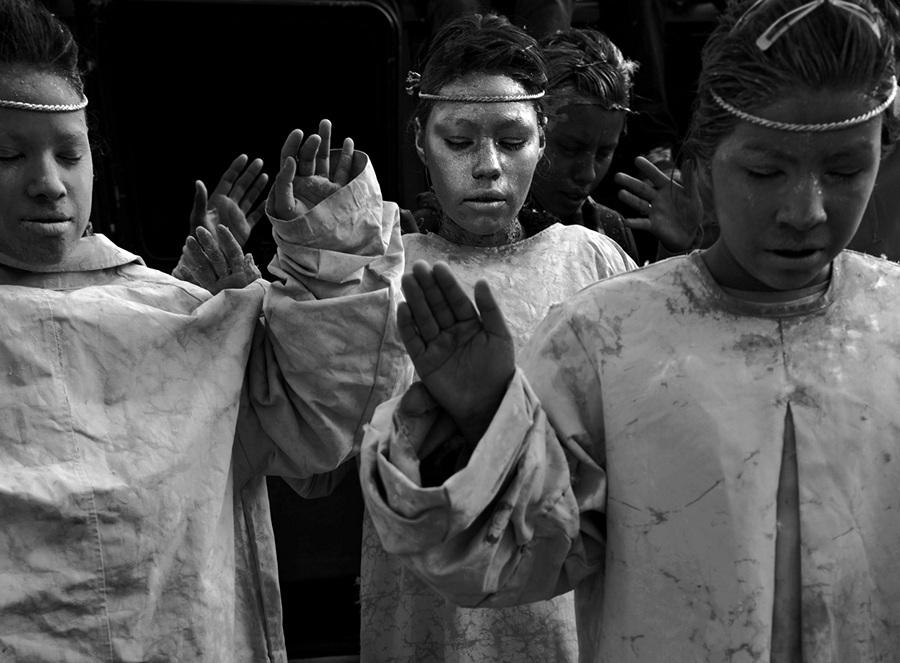 Мексика. Сьюдад-Хуарес, Чиуауа. Девочки в костюмах ангелов молятся на месте преступления, где молодой парень был убит во время так называемого «разогрева площади» конкурирующими наркокартелями. (Louie Palu/ZUMA Press)