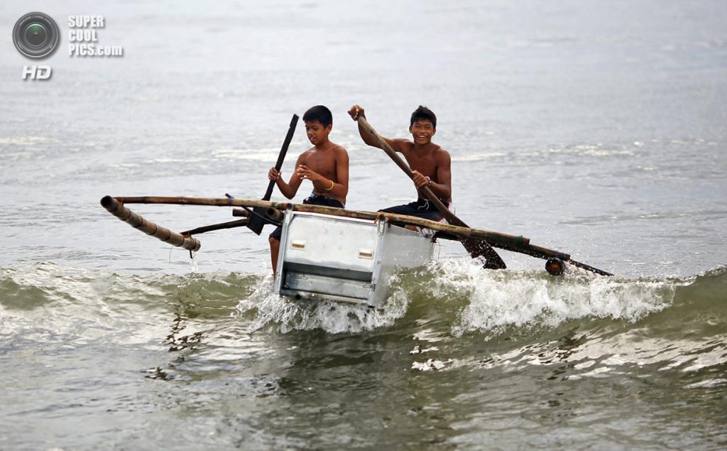 Филиппины. Танауан, Лейте. 20 ноября. Мальчики-рыбаки маневрируют на лодке, сделанной из поломанного холодильника и бамбука. (REUTERS/Damir Sagolj)