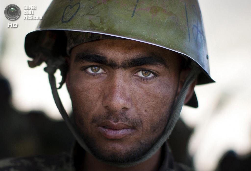 Афганистан. Кабул. 8 мая 2013 года. 20-летний Ахмад — солдат Афганской национальной армии — чистит свое оружие после тренировки в учебном центре. (AP Photo/Anja Niedringhaus)