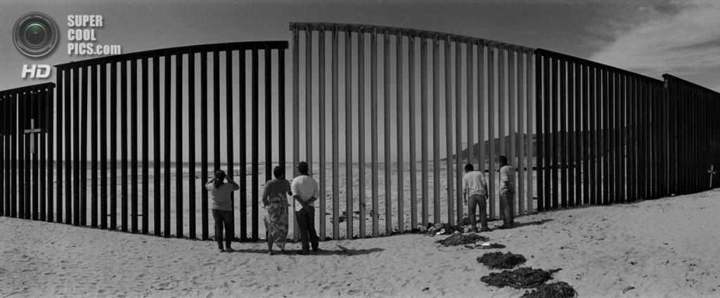 Мексика. Тихуана, Нижняя Калифорния. Мексиканцы выглядывают за забор на пляже вдоль американо-мексиканской границы. (Louie Palu/ZUMA Press)