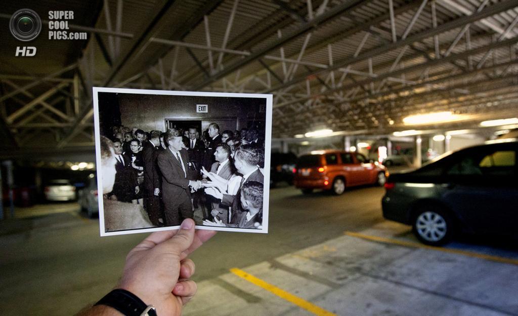 США. Даллас, Техас. 22 октября. Репортёр с фотографией Джона Кеннеди и его жены Жаклин на автостоянке отеля Rice Hotel. (AP Photo/Houston Chronicle, Cody Duty)