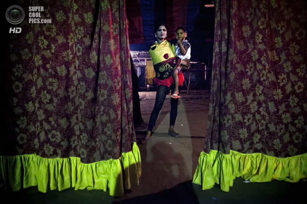 Бангладеш. Джамша. 31 октября. Баби Акхтер Султанг со своим трёхлетним сыном Шобуйхом наблюдает за преедставлением из-за кулис. Баби, которая не знает свой точный возраст, работает в цирке 6 лет. Ей не нравится здесь, но нужда не позволяет бросить работу. (Getty Images)