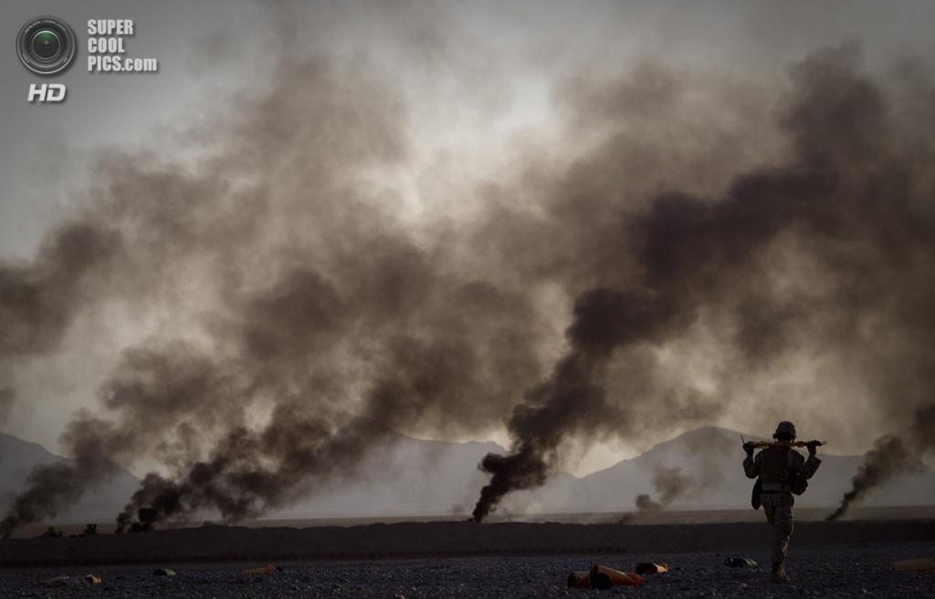 Афганистан. Гильменд. 9 июня 2011 года. Морской пехотинец забирает продовольствие, спущенное парашютом с самолёта. Дым на заднем плане исходит от сжигаемых парашютов. (AP Photo/Anja Niedringhaus)