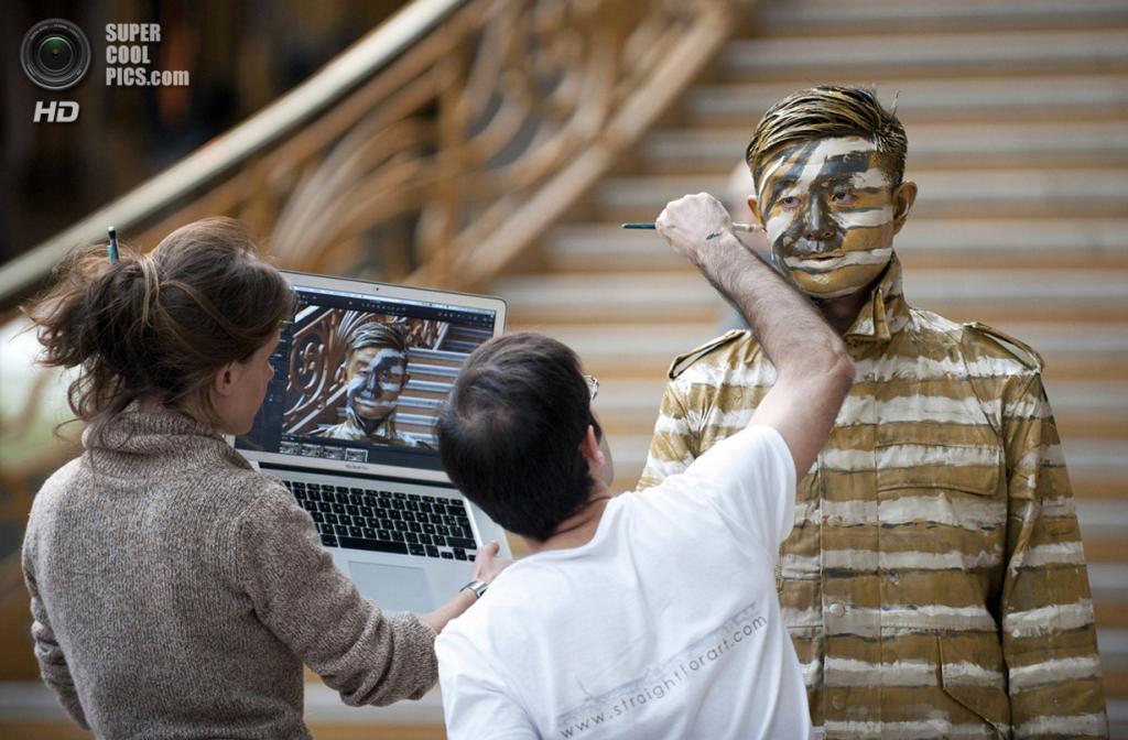 Франция. Париж. 1 апреля 2011 года. Художник Гийом Беаль наносит последние штрихи камуфляжа на лицо Лю Болиня, используя цифровой макет. (BERTRAND LANGLOIS/AFP/Getty Images)
