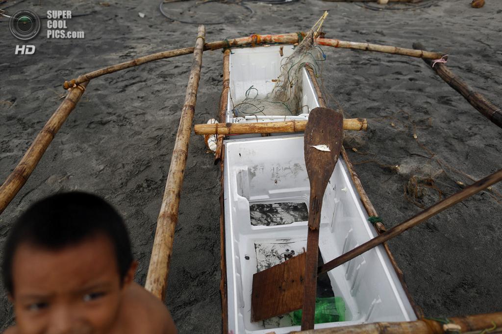 Филиппины. Танауан, Лейте. 20 ноября. Мальчик сидит на лодке, сделанной из поломанного холодильника и бамбука. (REUTERS/Damir Sagolj)