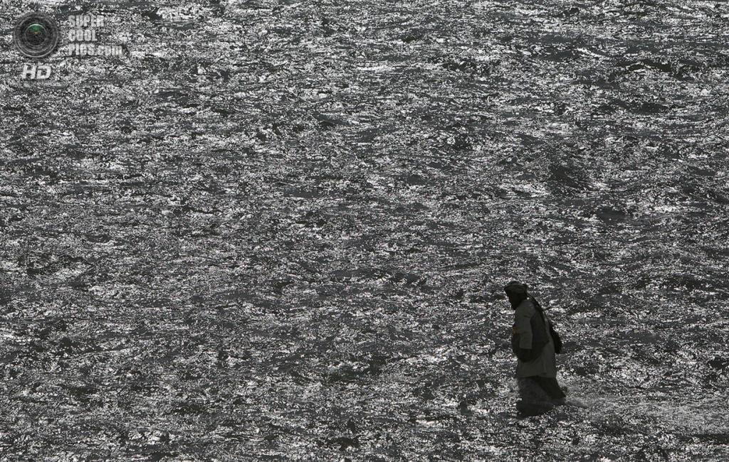 Афганистан. Фейзабад, Кундуз. 12 сентября 2009 года. Афганец бредёт по реке рядом с патрулём. (AP Photo/Anja Niedringhaus)