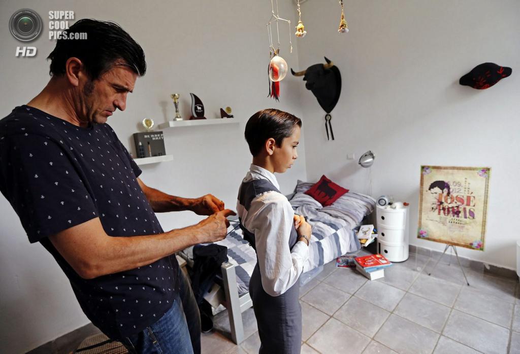 Франция. Ним, Гар. 5 октября. Отец помогает одеть костюм своему 12-летнему сыну Солалю перед бекеррадой — корридой для начинающих. (REUTERS/Jean-Paul Pelissier)