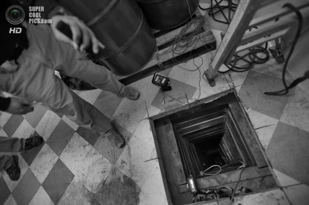 США. Сан-Луис, Аризона. Агент Управления по борьбе с наркотиками освещает 220-метровый туннель глубиной 17 метров, проходящий под американо-мексиканской границей. Предполагается, что его рыли около года и он обошёлся наркокартелю в $1 млн. (Louie Palu/ZUMA Press)