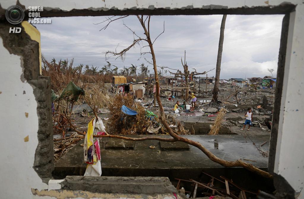 Филиппины. Танауан, Лейте. 20 ноября. Жители разрушенной деревни набирают питьевую воду на месте, где некогда стояла школа. (REUTERS/Damir Sagolj)