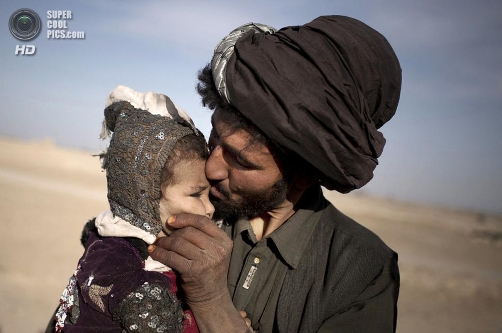 Афганистан. Марджа, Гильменд. 20 октября 2012 года. Афганский кочевник целует свою дочь, присматривая вместе с ней за стадом. (AP Photo/Anja Niedringhaus)