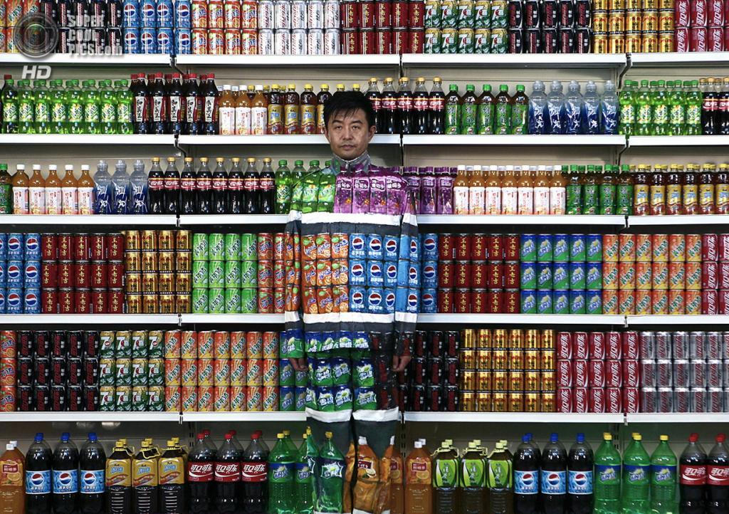 Китай. Пекин. 10 августа 2011 года. Лю Болинь на фоне стенда с прохладительными напитками в своей студии в «Арт-зоне 798». (AP Photo)
