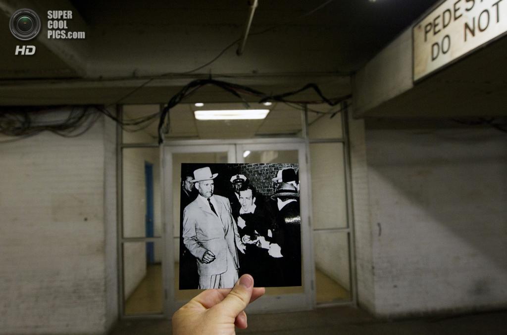 США. Даллас, Техас. 10 сентября. Репортёр с фотографией убийства Ли Харви Освальда — убийцы Джона Кеннеди. (AP Photo/Houston Chronicle, Cody Duty)