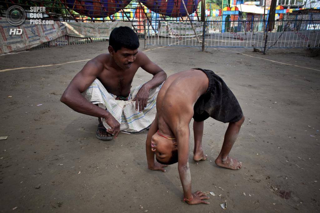 Бангладеш. Джамша. 1 ноября. 7-летний Нисхан практикуется под руководством Мухаммеда Мосхрума, своего отца, перед вечерними представлениями. (Getty Images)