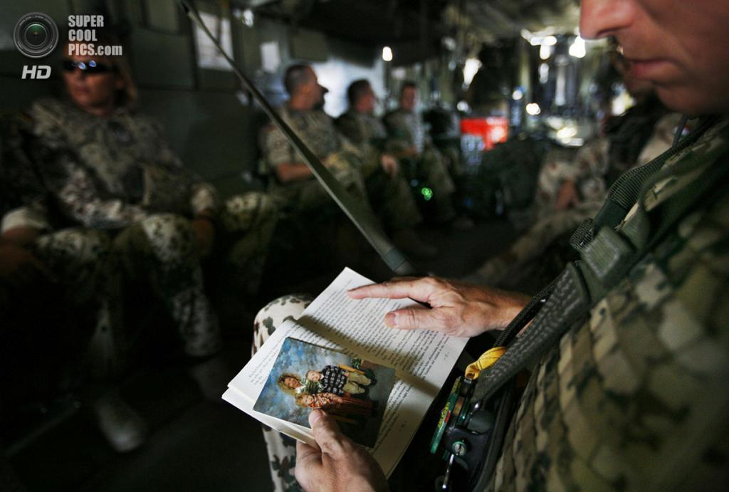 Афганистан. Фейзабад, Кундуз. 24 сентября 2008 года. Немецкий солдат использует фотографию своей семьи как закладку во время чтения на вертолёте CH-53. (AP Photo/Anja Niedringhaus)