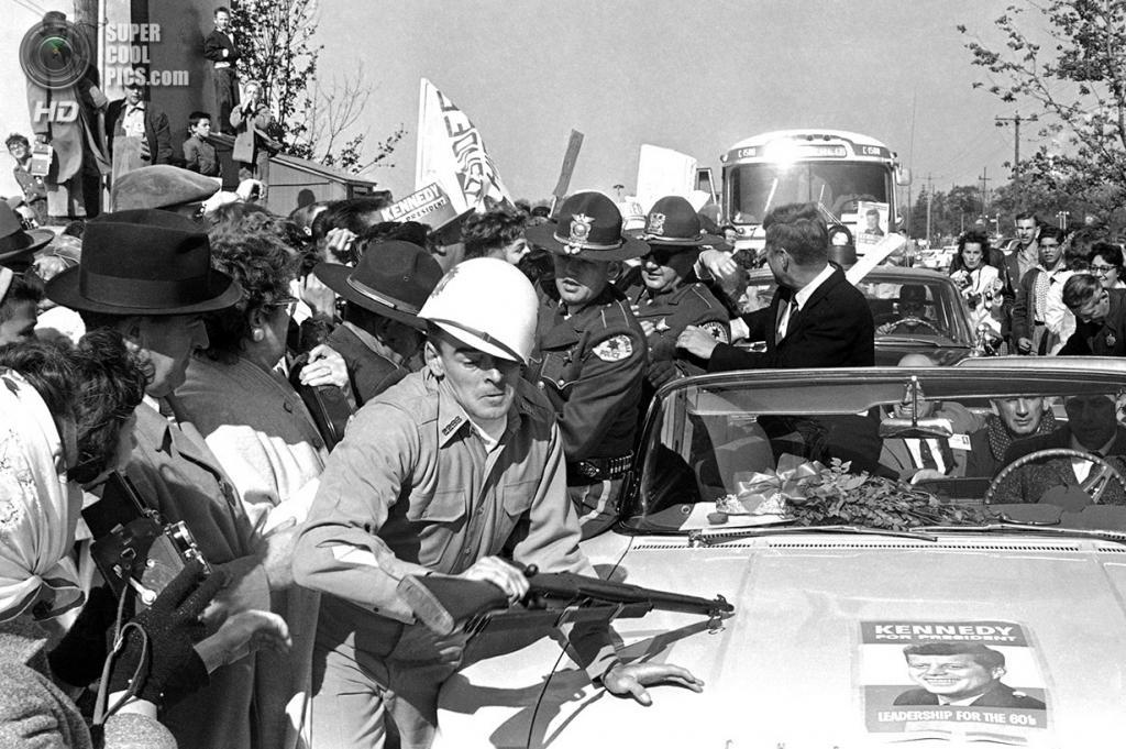 США. Элджин, Иллинойс. 25 октября 1960 года. Мужчина с ружьем в военной униформе смят в колонну автомобилей, везущих делегацию Джона Ф. Кеннеди. (AP Photo)