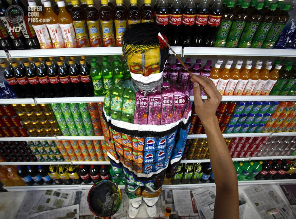 Китай. Пекин. 10 августа 2011 года. Коллеги Болиня доделывают камуфляж. (AP Photo)