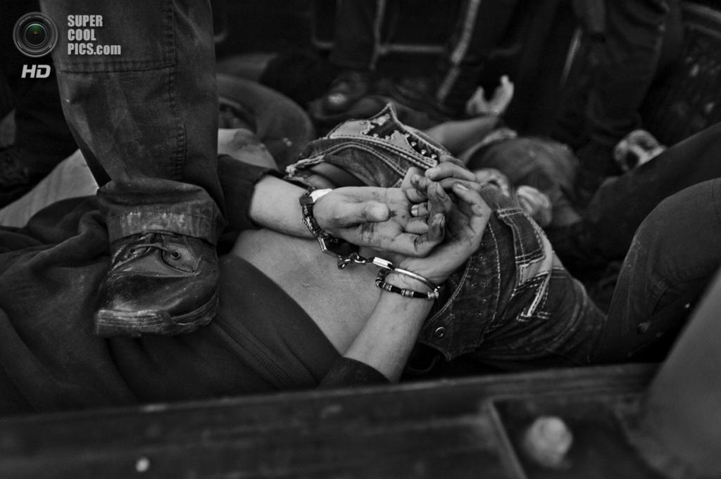 Мексика. Сьюдад-Хуарес, Чиуауа. Мексиканский полицейский стоит на спине арестованного члена наркокартеля, оказавшего сопротивление при аресте. Мексиканская полиция известна высоким процентом коррупции, частым нарушением прав человека и работой сообща с наркокартелями. В 2008 году только 38 % полицейских имело диплом об окончании средней школы. (Louie Palu/ZUMA Press)