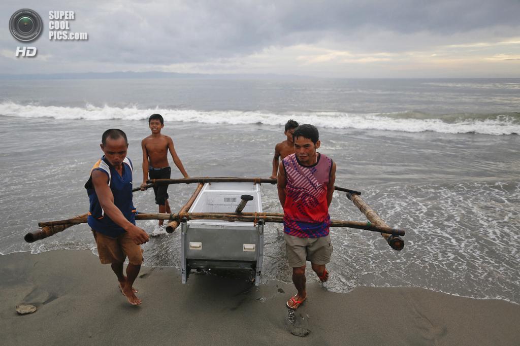 Филиппины. Танауан, Лейте. 20 ноября. Рыбаки вытаскивают лодку на берег. (REUTERS/Damir Sagolj)