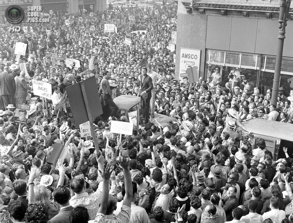 США. Лос-Анджелес, Калифорния. 1 ноября 1960 года. Сенатор Джон Ф. Кеннеди стоит на капоте грузовика, чтобы приветствовать своих доброжелателей. (AP Photo)