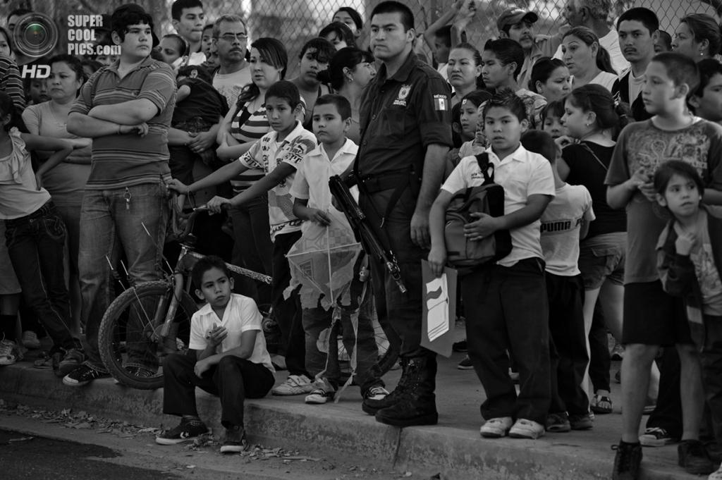 Мексика. Кулиакан, Синалоа. Дети, окружив полицейского, разглядывают место преступления прямо у входа на территорию школы. (Louie Palu/ZUMA Press)