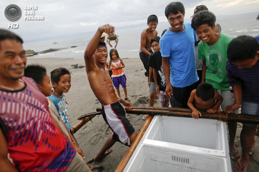 Филиппины. Танауан, Лейте. 20 ноября. Парень демонстрирует краба, найденного на дне лодки. (REUTERS/Damir Sagolj)