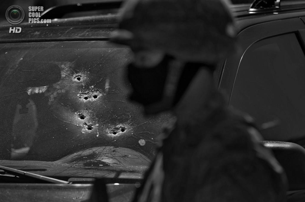 Мексика. Кулиакан, Синалоа. Солдат на страже обстрелянного автомобиля, в котором были найдены тела двух человек, убитых, предположительно, в перестрелке наркокартелей. (Louie Palu/ZUMA Press)