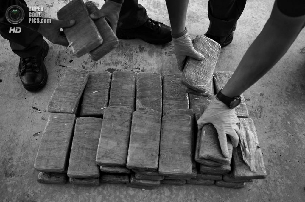США. Ларедо, Техас. Пограничник складывает упаковки марихуаны, конфискованные на американо-мексиканской границе. (Louie Palu/ZUMA Press)