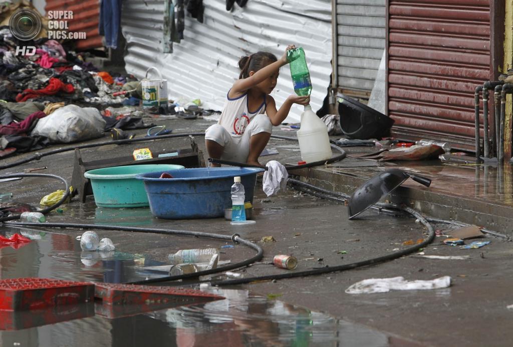 Филиппины. Таклобан. 12 ноября. Девочка набирает питьевую воду. (REUTERS/Romeo Ranoco)