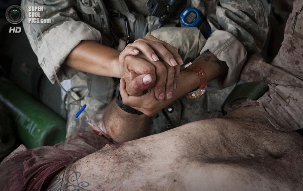 Афганистан. Сангин, Гильменд. 4 июня 2011 года. Дженни Мартинес держит за руку Бёрнесса Бритта, раненого шрапнелью в шею и голову, во время первой операции после инцидента. (AP Photo/Anja Niedringhaus)