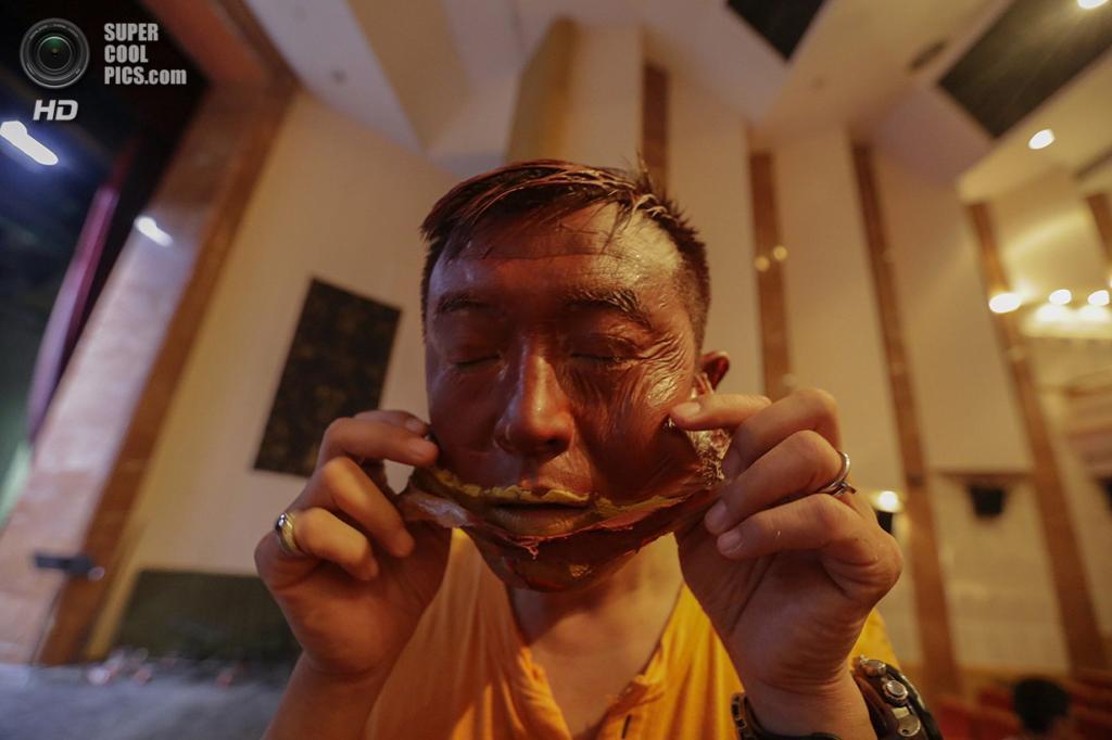 Китай. Пекин. 12 сентября 2013 года. Лю Болинь снимает обрисованную маску. (REUTERS/Jason Lee)