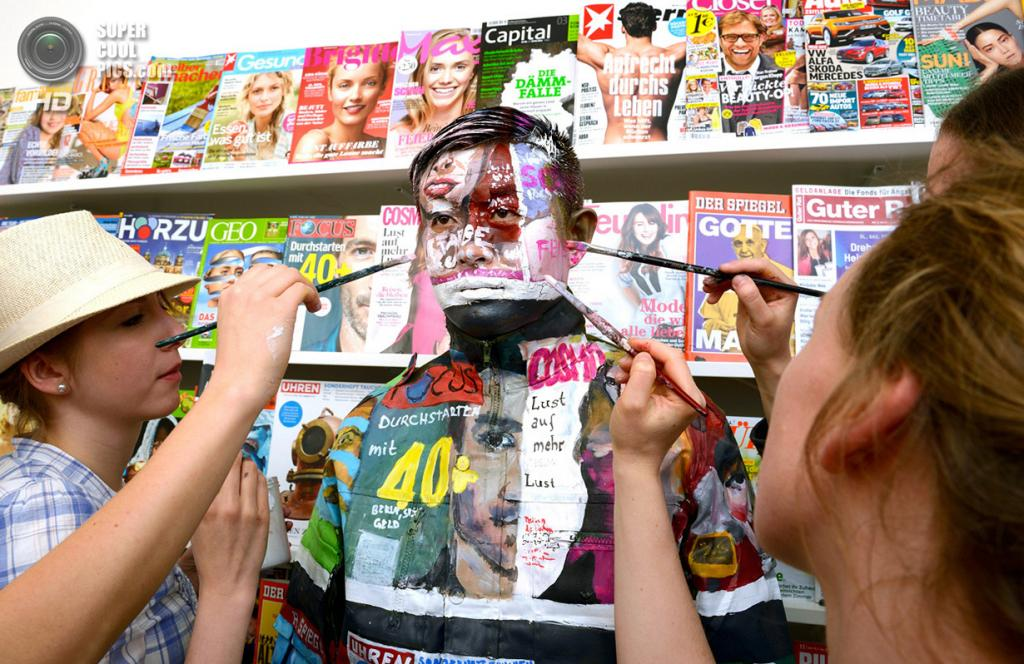 Германия. Людвигсбург, Баден-Вюртемберг. 15 мая 2013 года. Студенты Штутгартской академии искусств обрисовывают Лю Болиня на фоне стенда с журналами. (BERND WEISSBROD/AFP/Getty Images)