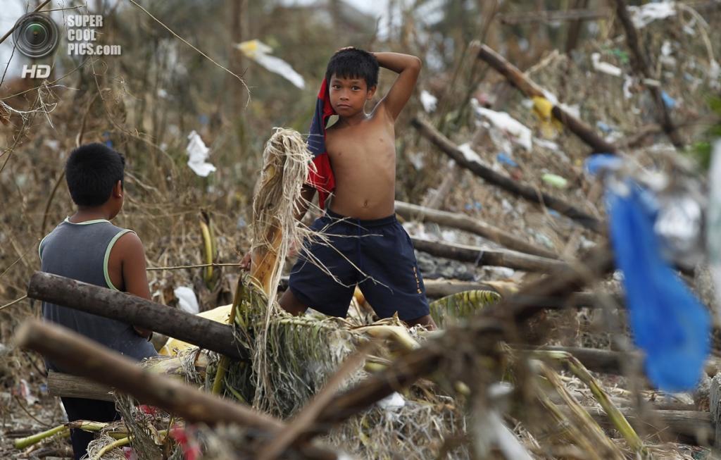 Филиппины. Таклобан. 11 ноября. Дети ковыряются в обломках в поисках уцелевших вещей. (AP Photo/Wally Santana)