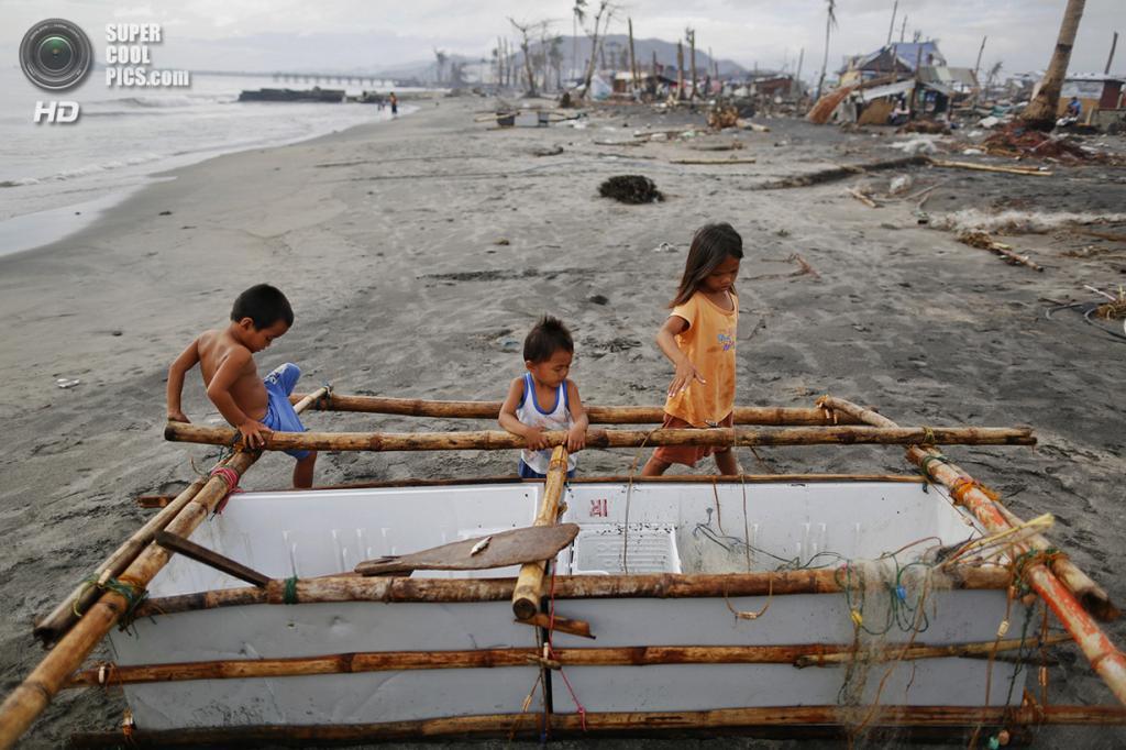 Филиппины. Танауан, Лейте. 20 ноября. Дети играют в лодке, сделанной из поломанного холодильника и бамбука. (REUTERS/Damir Sagolj)